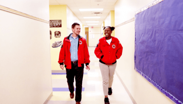 An AmeriCorps member and her Impact Manager walk down the hallway