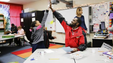 City Year AmeriCorps member high five with student