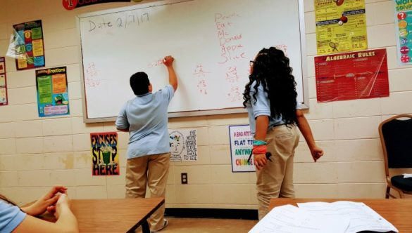 students solving math problems at a white board