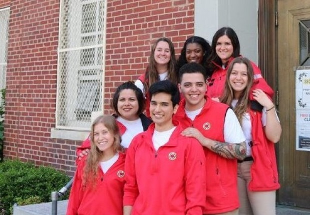 A team of eight AmeriCorps members huddled together smiling on the stairs in front of their school