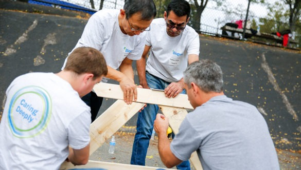 A group of volunteers work on an outdoor project at a school.