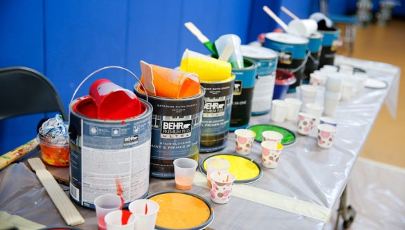 Cans of paint are lined up and ready for volunteers to begin painting.