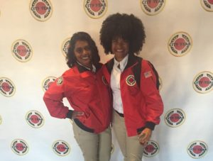 Two AmeriCorps Members pose in front of a backdrop decorated with City Year logos