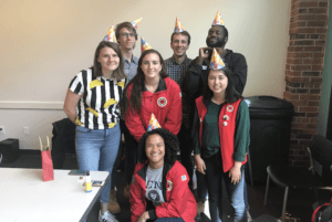 A group of seven team leaders wear cone-shaped party hats and smile at the camera.