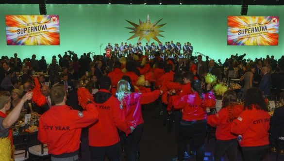 AmeriCorps members flank the aisles as they cheer at a City Year event