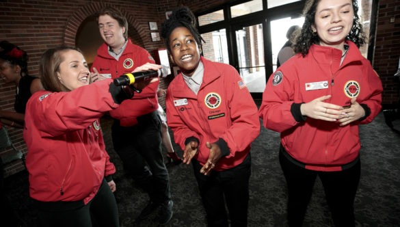 AmeriCorps members dancing and singing into a microphone
