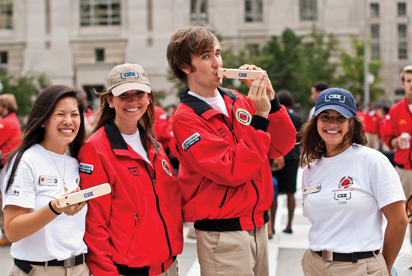 Four AmeriCorps members wearing and holding CSX branded items