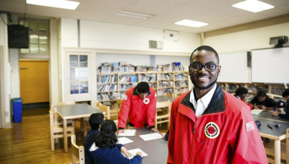 A City Year AmeriCorps member stand in a library, looking proudly at the camera. Behind him are students working on homework with another AmeriCorps member