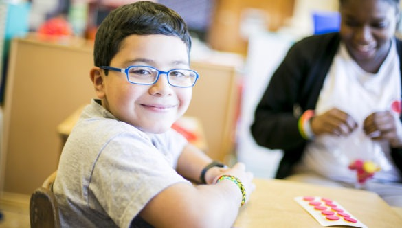 smiling elementary student doing a project at a table with an AmeriCorps member