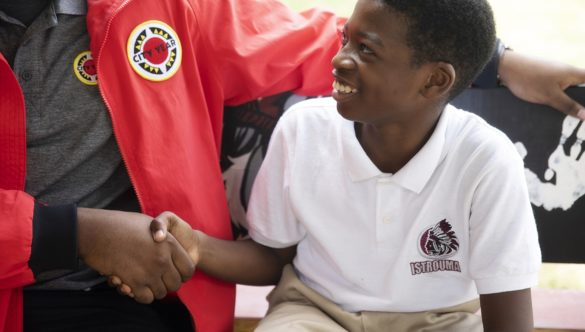 a young student smiles and looks up at an AmeriCorps member while shaking their hand