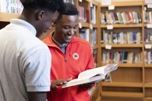 an AmeriCorps member is holding a book and reading with a student in the library