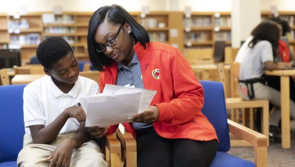 AmeriCorps member reviewing papers with a student in the library