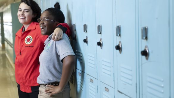 An AmeriCorps member is standing with a student next to lockers and both are laughing