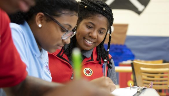 two students are doing independent work at a table while an AmeriCorps member looks at their work and smiles