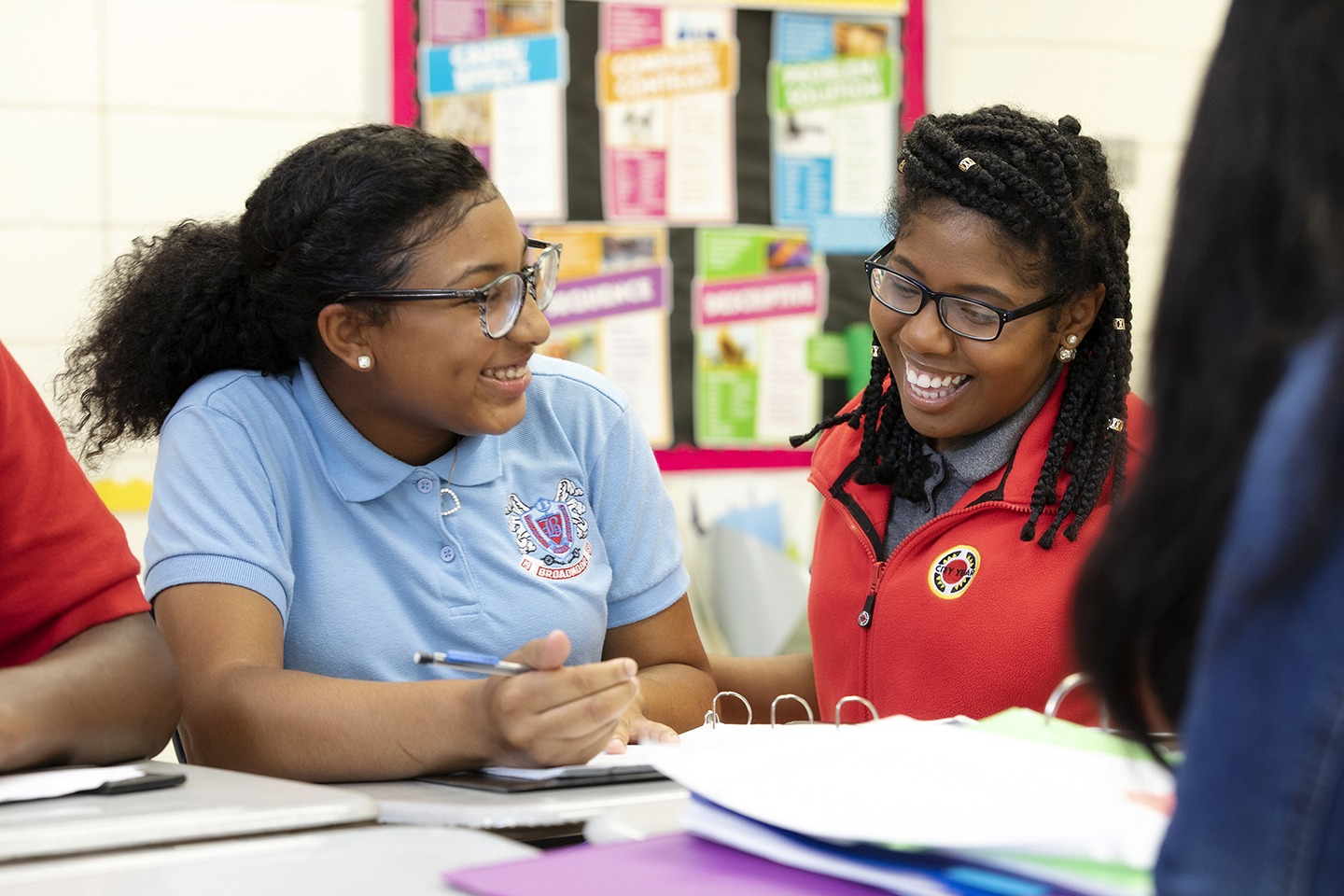 a student smiles and looks at an AmeriCorps member as they sit together at a table doing work