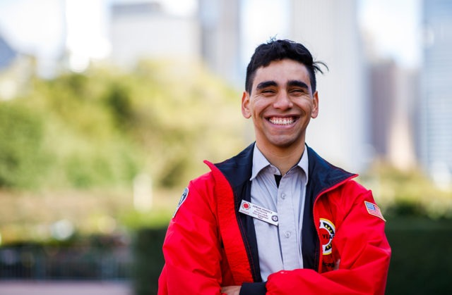 An AmeriCorps member stands in a park with the city skyline in the background.
