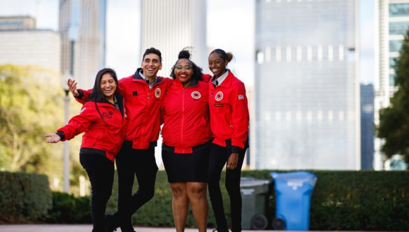 A group of AmeriCorps members pose together in the park with the skyline in the background.