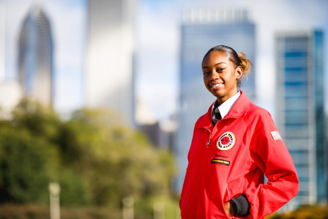 An AmeriCorps member stands in front of the city skyline.