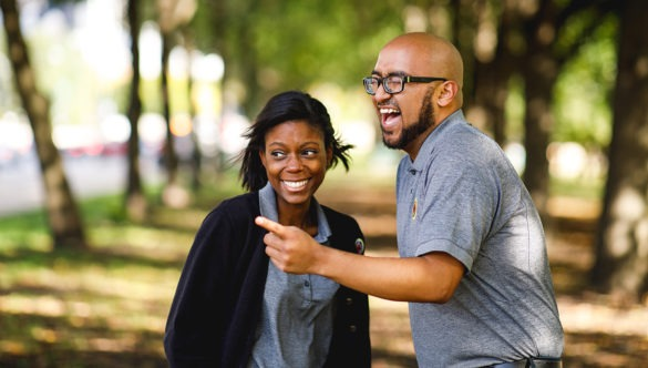 Two AmeriCorps members share a laugh at a city park.