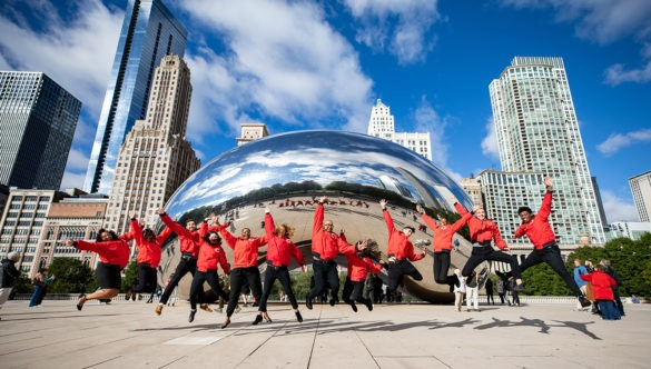A group of AmeriCorps members jump and cheer in front of the city skyline.