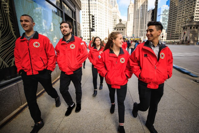 A group of AmeriCorps members walk along the city sidewalk.