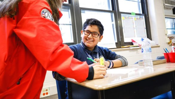 an elementary student is working at desk while AmeriCorps member is standing by to help