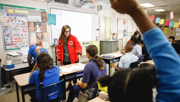 elementary students are in classroom with hands raised while AmeriCorps member rotates through and talks to students