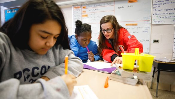 an AmeriCorps member is leaning over to point out something on a student's paper while they work on an assignment in class