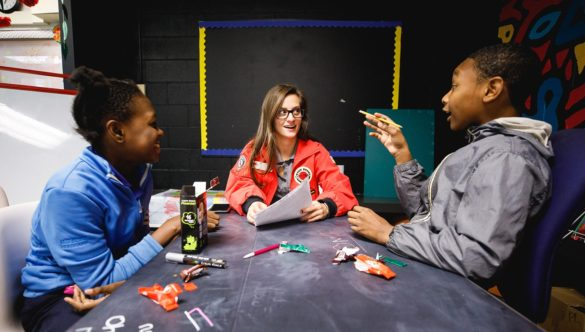 two students are sitting at a work table in a conversation with an AmeriCorps member