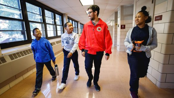 AmeriCorps member walks with three students in the hallway