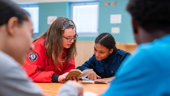 AmeriCorps member and students are reading a novel together at a table