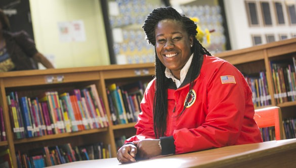 An AmeriCorps member sits at a table in a school library.
