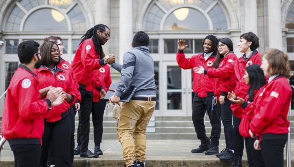 A group of AmeriCorps members line up outside of school to greet students with high-fives.
