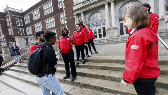 City Year AmeriCorps members create a welcome tunnel down both sides of the school's front steps