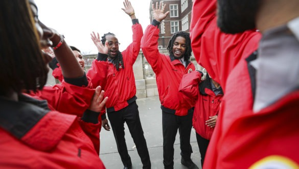 A team of City Year AmeriCorps members raise their hands at the end of a team huddle