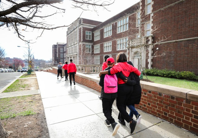 Two students with backpacks walking on a sidewalk near a school with a City Year Corps Member