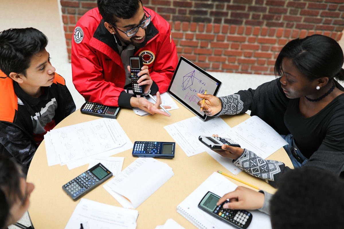 Four students with calculator, and papers with a City Year Corps Member who is showing a geometry problem