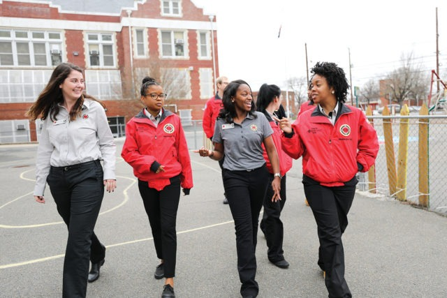 A group of AmeriCorps members chat as they walk across the school playground.