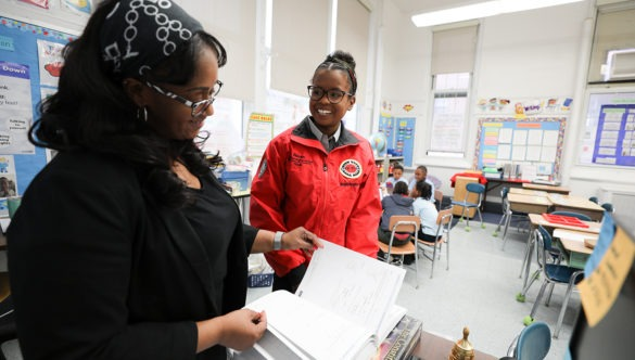 A city year corps member with a teacher in a classroom with students in a circle in the back ground