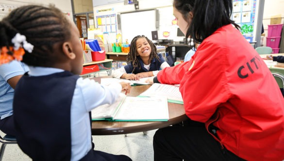 two young students, one smiling in a classroom as a City Year corps member teaches them around a table in a classroom
