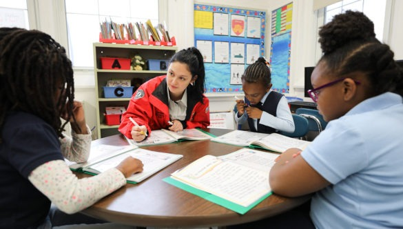 Three students listening at a table as a City Year corps member helps them with their work