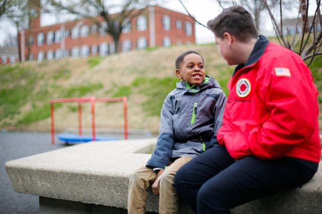 A young student in a jacket sitting with a city year corps member in a school playground in the winter