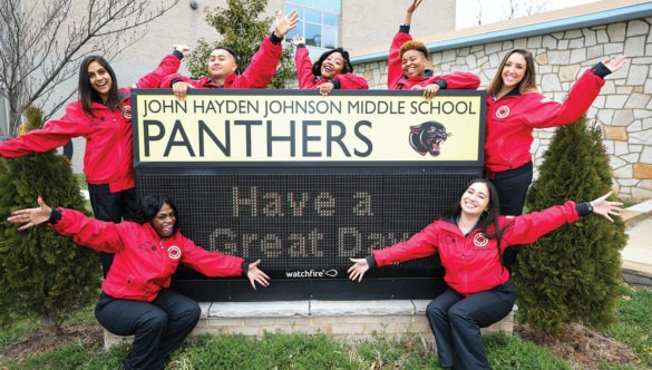 AmeriCorps members wave their hands in front of the entrance sign to a middle school.
