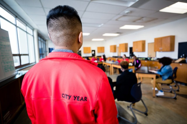 the back of a city year americorp member with the label City Year on his jacket as he looks over a teacher and students in a classroom