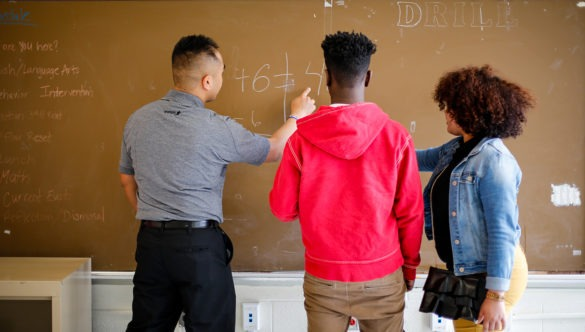 A city year americorps member at a chalkboard showing a math problem to two high school students