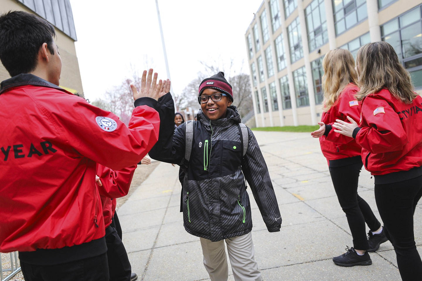 An elementary school student wearing glasses high fives a City Year AmeriCorps member outside their school