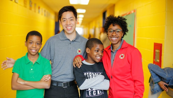 Two city year americorps members posing with two young students in a school hallway.