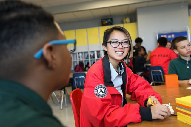 City year americorps member sitting at a table with a student with students and corps members in the background