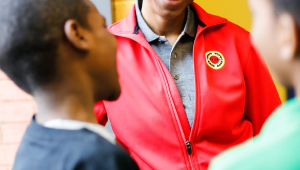 City year americorps member talking with two young students near a window in a school hallway
