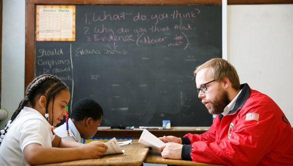 City year americorps member reading along with two students as they sit at desks in a classroom